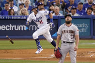 Los Angeles Dodgers' AJ Pollock, left, runs to first after hitting a solo home run as Arizona Diamondbacks starting pitcher Caleb Smith watches during the first inning of a baseball game Saturday, July 10, 2021, in Los Angeles. (AP Photo/Mark J. Terrill)