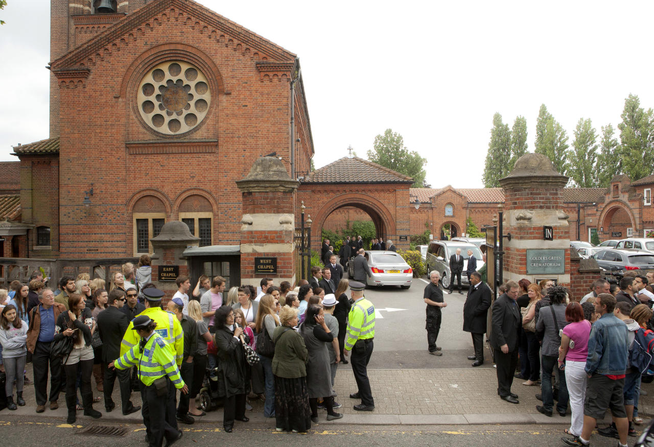 Members of the public gather opposite Golders Green Crematorium for the funeral ceremony of British singer Amy Winehouse, north London, Tuesday, July 26, 2011. Winehouse, who had battled alcohol and drug addiction, was found dead Saturday at her London home. She was 27. (AP Photo/Joel Ryan)