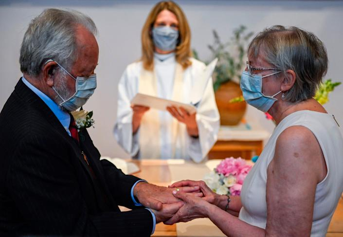 Bride Linda Delk places a ring on her groom Ardell Hoveskeland during a May 28, 2020 ceremony in Alexandria, Virginia, led by Pastor Sarah Scherschligt.