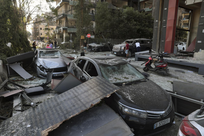 People inspect their damaged cars after a massive explosion on Tuesday, in Beirut, Lebanon, Wednesday, Aug. 5, 2020. The explosion flattened much of a port and damaged buildings across Beirut, sending a giant mushroom cloud into the sky. In addition to those who died, more than 3,000 other people were injured, with bodies buried in the rubble, officials said. (AP Photo/Bilal Hussein)