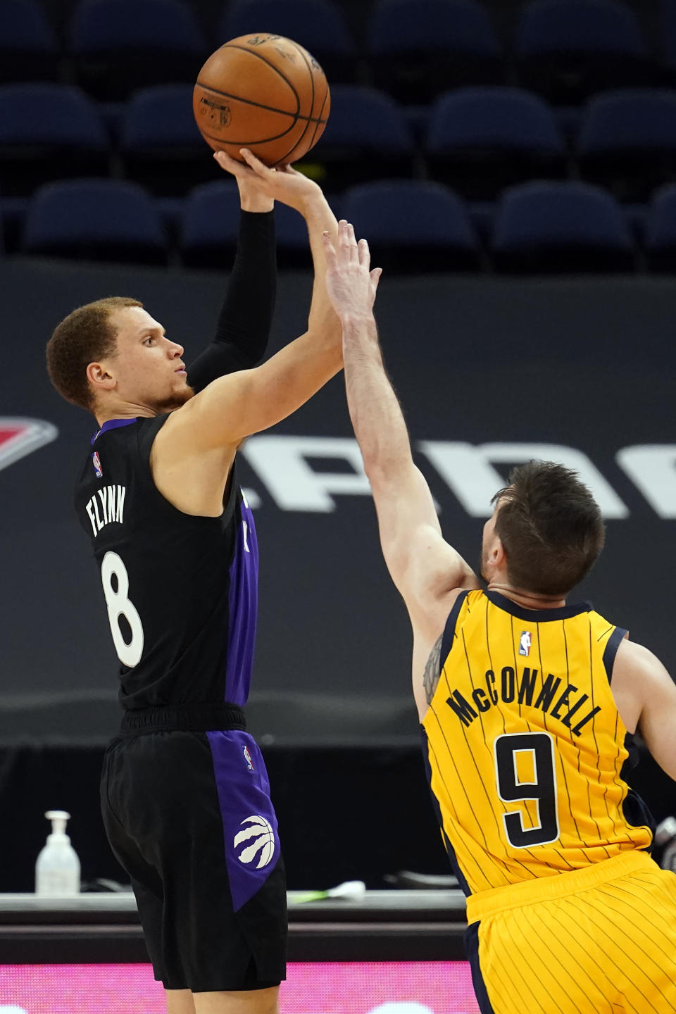Toronto Raptors guard Malachi Flynn (8) puts up a three-point shot over Indiana Pacers guard T.J. McConnell (9) during the second half of an NBA basketball game Sunday, May 16, 2021, in Tampa, Fla. (AP Photo/Chris O'Meara)