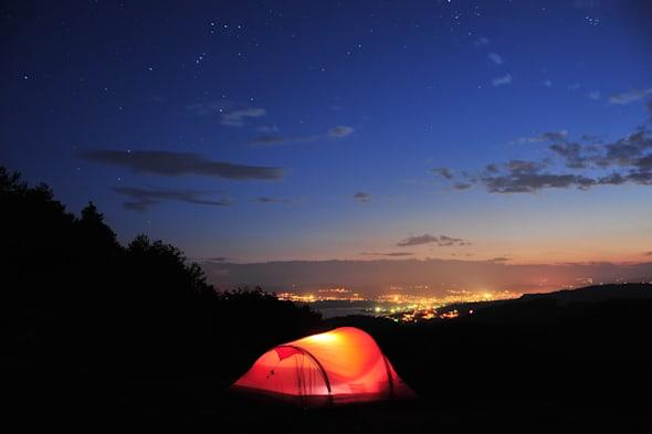 Camping at night. Lighted tent under the stars in mountains, with city lights in background, Bulgaria.