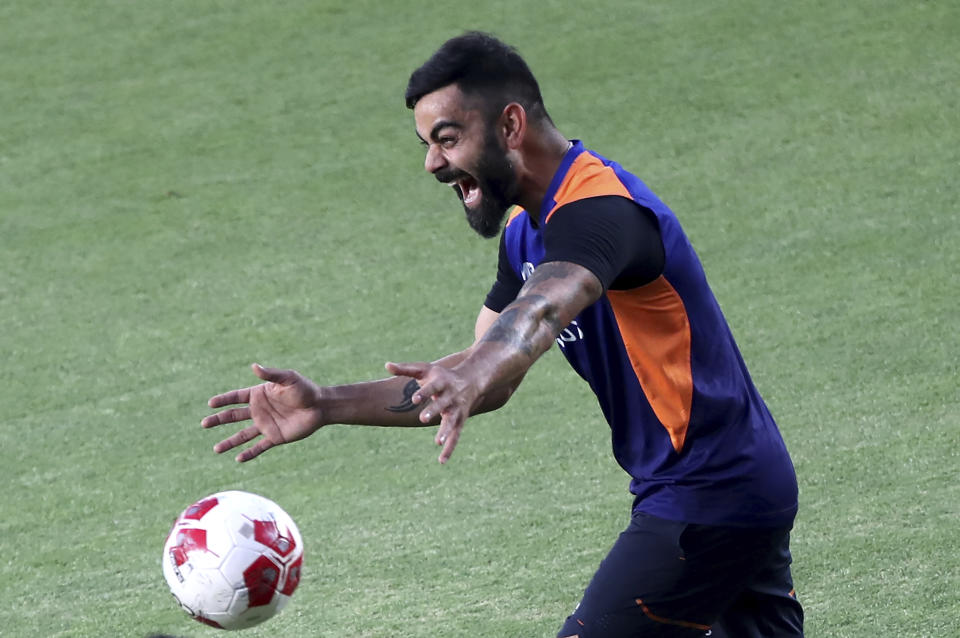 India's captain Virat Kohli laughs as he reacts to his teammates during a training session ahead of the first Twenty20 cricket match between India and England in Ahmedabad, India, Monday, March 8, 2021. (AP Photo/Aijaz Rahi)