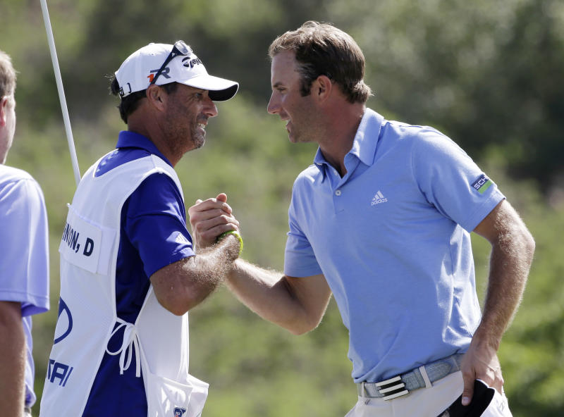Dustin Johnson, right, is congratulated by his caddie, Bobby Brown, after winning the Tournament of Champions PGA golf tournament Tuesday, Jan. 8, 2013, in Kapalua, Hawaii. Johnson finished at 16-under 203. (AP Photo/Elaine Thompson)