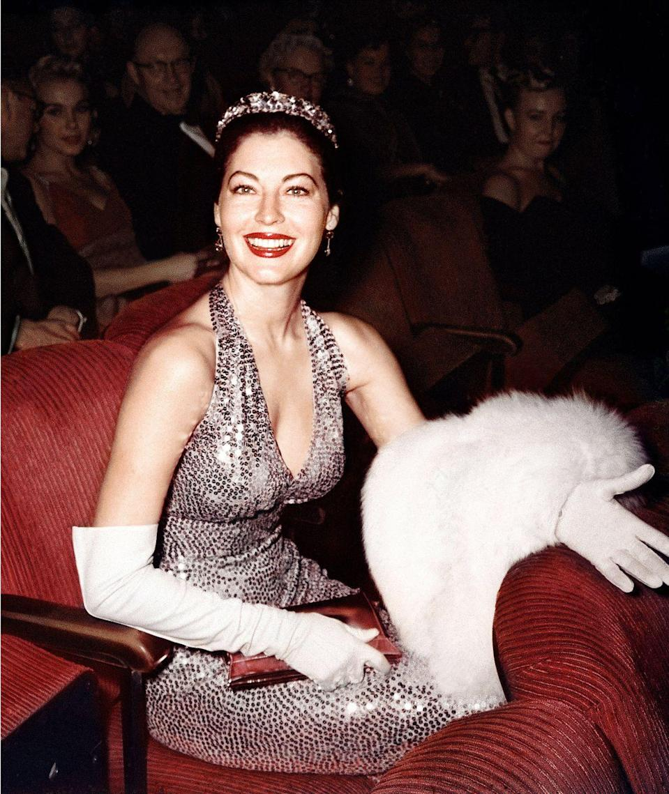 <p>Ava Gardner looks like Hollywood royalty in a bejeweled gown, elegant gloves, and tiara. </p>