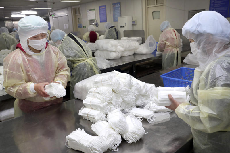 Workers package medical masks in a factory in Nantong in eastern China's Jiangsu Province, Monday, Jan. 27, 2020. China on Monday expanded sweeping efforts to contain a viral disease by extending the Lunar New Year holiday to keep the public at home and avoid spreading infection. (Chinatopix via AP)