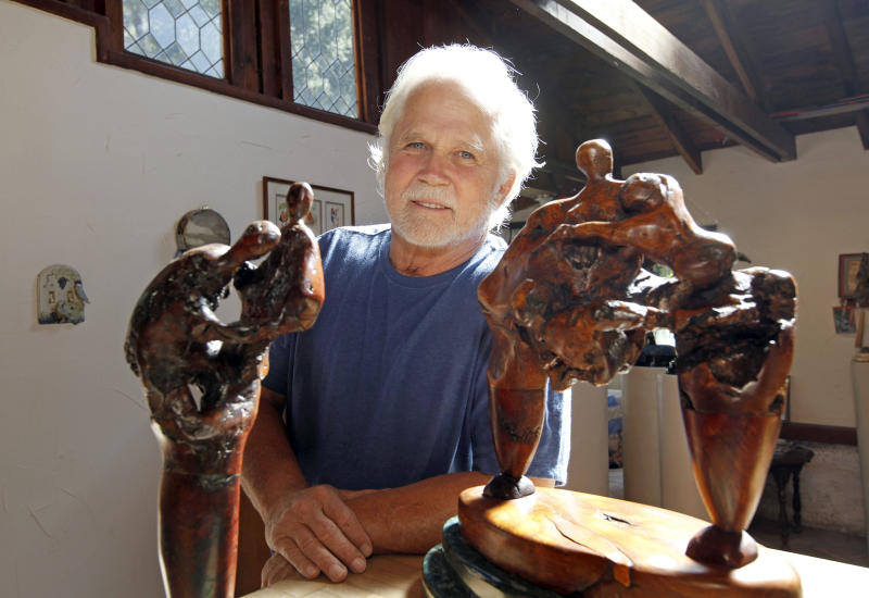 """In this Thursday, Sept. 18, 2012 photo, Tony Dow, actor, director and artist, poses with, from left, Two Figures and Struggle, at his home and studio in the Topanga area of Los Angeles. When it comes time to sitting down in a studio and carving out bronze and wooden sculptures inspired by the nature all around him, Wally isn't leaving it up to the Beav these days. Dow, who famously played the Beaver's older brother Wally on the classic 1950s-60s sitcom """"Leave it To Beaver,"""" is carving out a name for himself in the art world these days, as an abstract artist. (AP Photo/Reed Saxon)"""