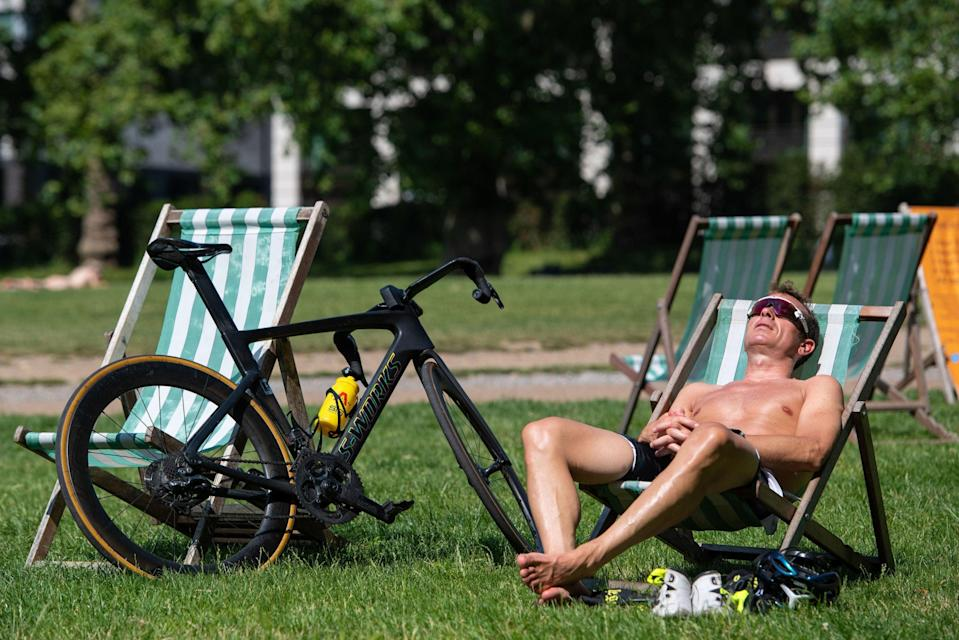 Flooding was probably the last thing on this man's mind as he enjoyed the heat in Green Park on Tuesday (PA)