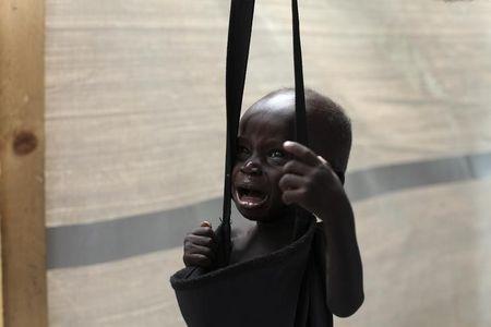 A South Sudanese child, suspected of malnutrition, cries while being weighed at a feeding center in Lul, Fashoda county