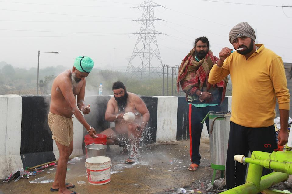 Indian farmers take bath during their ongoing sit-in farmers protest at the Delhi-Uttar Pradesh border, India, on December 30, 2020. (Photo by Pankaj Nangia/Anadolu Agency via Getty Images)