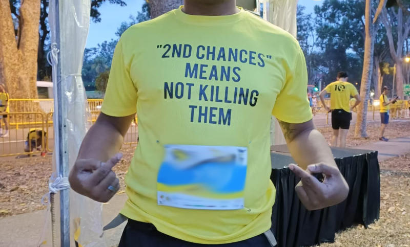 """The duo had turned up at the venue wearing t-shirts with the words """"2ND CHANCES MEANS NOT KILLING THEM"""" printed on the front of the t-shirts, and """"#ANTIDEATHPENALTY"""" printed on the back. (PHOTO: Social media)"""