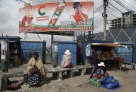 A billboard promoting presidential candidate Carlos Mesa of the Citizen Community political party towers over a trio of women in Rio Seco, Bolivia, Saturday, Oct. 17, 2020. Sunday's presidential election gives Bolivians a chance for a political reset as they struggle with the dramatic costs of the COVID-19 pandemic. (AP Photo/Martin Mejia)