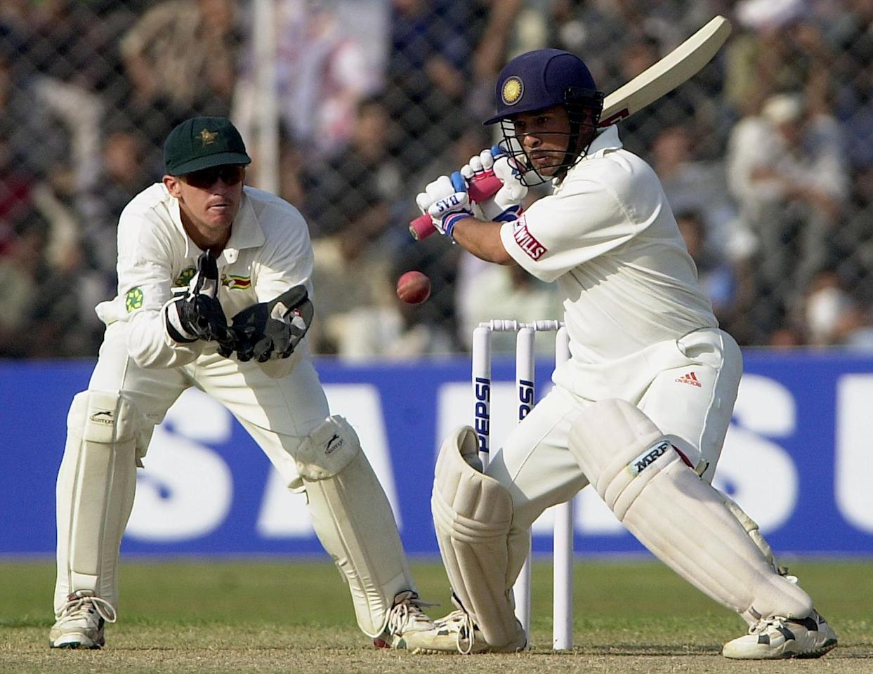 Indian ace batsman Sachin Tendulkar (R) about to whip a delivery from Zimbabwean spinner Brian Murphy (not in the picture) to the fence as Zimbabwean wicketkeeper Andy Flower looks on during the third's days play in the first test match betwen India and Zimbabwe in New Delhi, 20 November 2000 at the  Ferozshah Kotla ground in New Delhi. India finished the day's play at 225 runs for two wickets in reply to Zimbabwe's total of 432 runs. AFP PHOTO ARKO DATTA