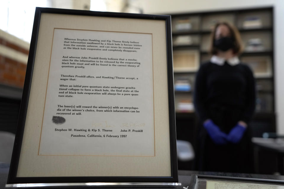 A letter and bet made by Professor Stephen Hawking and Kip Thorne with John Preskill on whether information can be recovered from a black hole, signed with Hawking's thumbprint, which has been acquired by the Science Museum Group, in London, Wednesday, May 26, 2021. Science Museum Group and Cambridge University Library will announce that they have acquired the historic contents of Professor Stephen Hawking's office (going to SMG) and his archive (going to CUL). (AP Photo/Kirsty Wigglesworth)