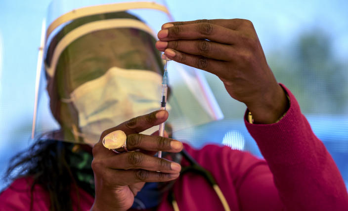 A health worker prepares a dose of the Pfizer coronavirus vaccine at the newly-opened mass vaccination program for the elderly at a drive-thru vaccination center outside Johannesburg, South Africa, Tuesday, May 25, 2021. South Africa aims to vaccinate 5 million of its older citizens by the end of June. (AP Photo/Themba Hadebe)