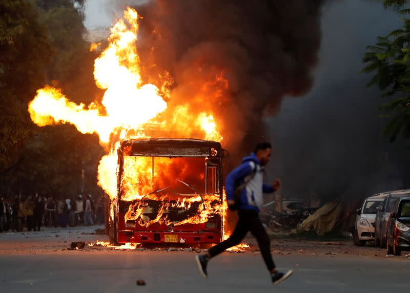 A man runs past a burning bus that was set on fire by demonstrators during a protest against a new citizenship law, in New Delhi