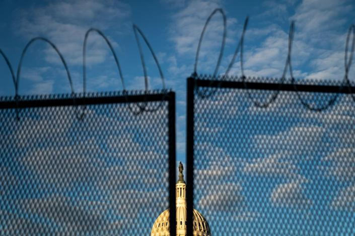 Barbed wire is seen atop security fencing, with the dome of the U.S. Capitol Building Saturday.