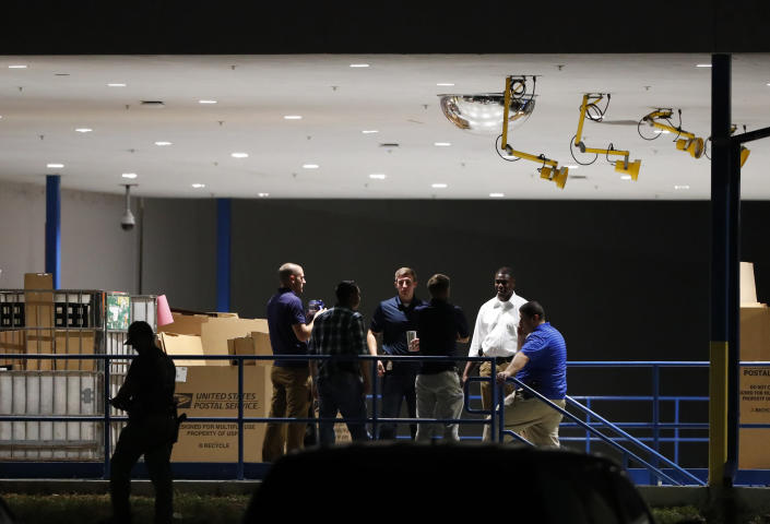 <p>People gather on a loading dock at a postal facility, Thursday, Oct. 25, 2018, in Opa-Locka, Fla. Investigators searched coast-to-coast Thursday for the culprit and motives behind the bizarre mail-bomb plot aimed at critics of the president. (Photo: Wilfredo Lee/AP) </p>