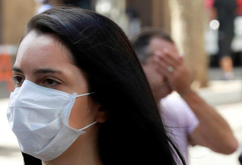 A woman walks as she wears a protective mask during the coronavirus disease (COVID-19) outbreak in downtown Porto Alegre