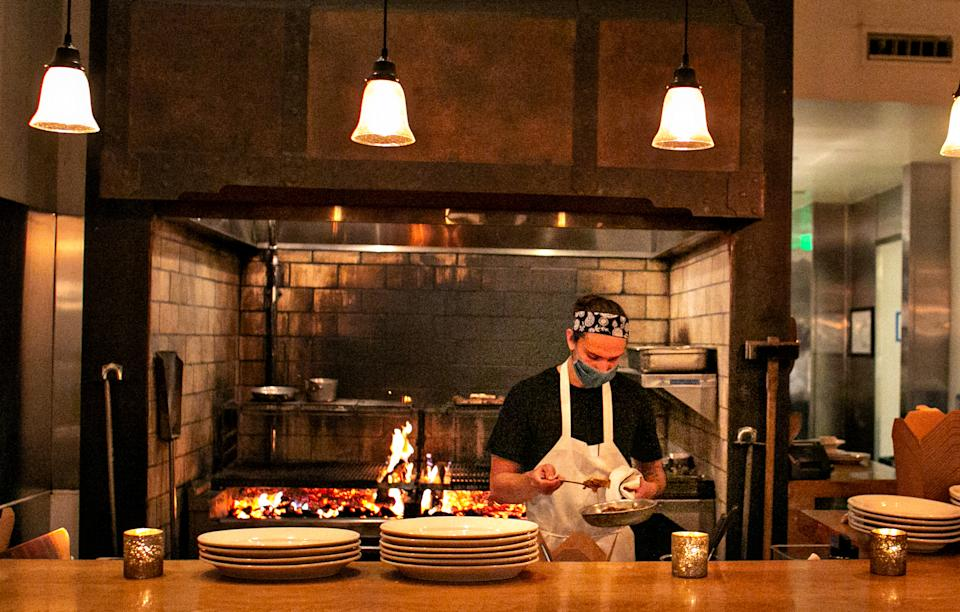 SANTA MONICA, CA - MAY 05: GJ Stinson, chef de tournant at Cassia, works the wood fire grills station as the much loved restaurant re-opens its indoor dining and continues outdoor dining on Wednesday, May 5, 2021 in Santa Monica, CA. (Jason Armond / Los Angeles Times via Getty Images)
