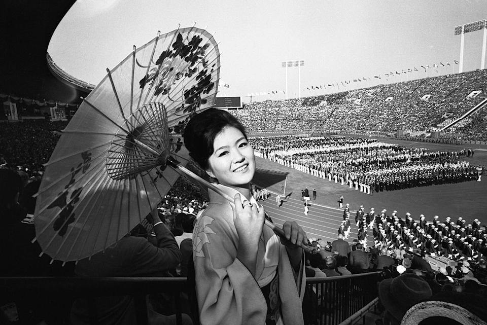 <p>Yuko Shibayama of Tokyo wears traditional garb to watch the colorful opening ceremonies of the 18th Olympiad at the National Stadium.</p>