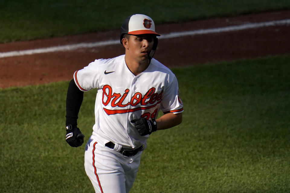 Baltimore Orioles' Ramon Urias heads to the dugout after hitting a two-run home run off Seattle Mariners starting pitcher Justus Sheffield during the fifth inning of the first game of a baseball doubleheader, Tuesday, April 13, 2021, in Baltimore. Orioles' DJ Stewart scored on the home run. (AP Photo/Julio Cortez)