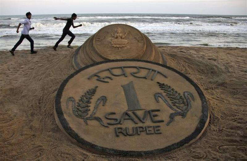 Boys run near a sand sculpture of the rupee created by sand artist Sudarshan Pattnaik at golden sea beach at Puri in the eastern Indian state of Odisha August 22, 2013. REUTERS/Stringer