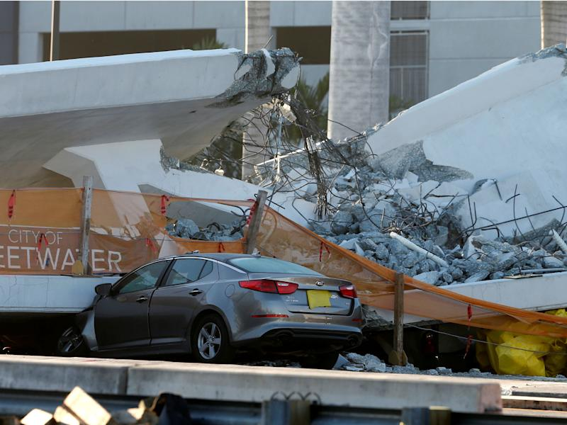 A damaged car partially crushed under a collapsed pedestrian bridge near Florida International University in Miami: Reuters