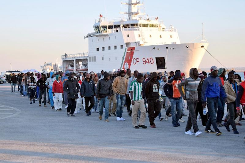 Shipwrecked migrants disembark from a rescue vessel as they arrive in the Italian island of Sicily, on April 16, 2015