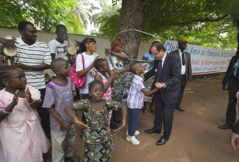 "France's President Francois Hollande, right, is welcomed by supporters outside of the French ambassador's residence in Bamako, Mali, Thursday, Sept. 19, 2013. World leaders and politicians from various countries are in Bamako to attend the ceremony as Boubacar Keita officially becomes Mali's president. Hollande declared during his speech Thursday that the war on terror had been won in the West African nation of Mali. Banner reads, ""friends of Francois Hollande Club, welcome in Mali"". (AP Photo/Michel Euler, Pool)"