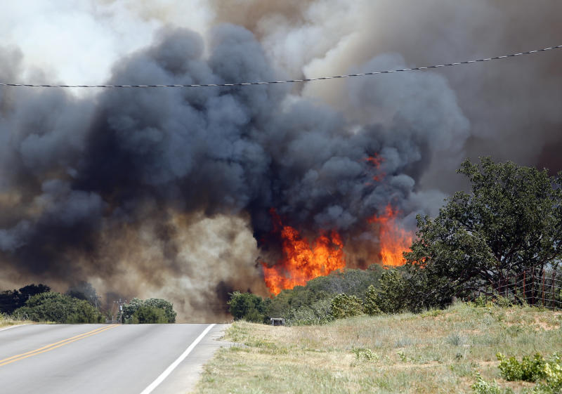 Flames leap into the air as area firefighters fight a wildfire on Cemetery Road east of 120th on Friday, Aug. 3, 2012, east of Norman, Okla.  A wildfire stirred by high winds sweeping through rural woodlands just south of the Oklahoma City area has set at a number of homes on fire.  (AP Photo/The Oklahoman, Steve Sisney) TABLOIDS OUT