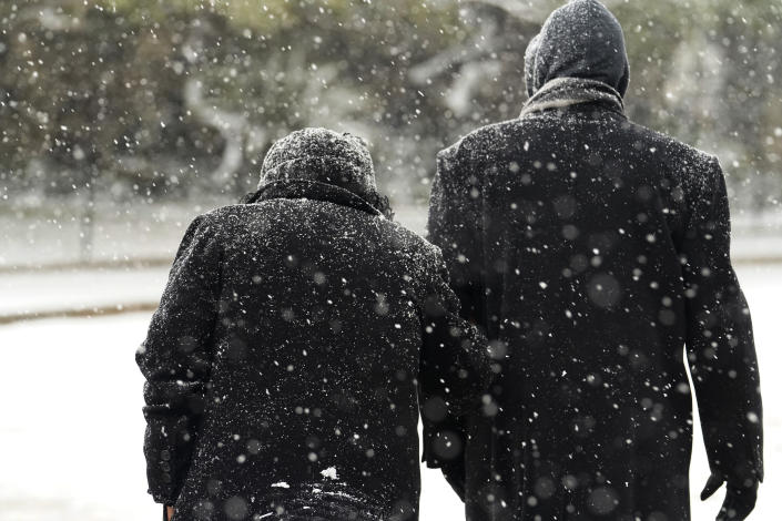 A couple walk through falling snow, Thursday, Feb. 18, 2021, in downtown San Antonio. Snow, ice and sub-freezing weather continue to wreak havoc on the state's power grid and utilities. (AP Photo/Eric Gay)