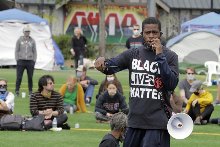 FILE - In this photo taken June 20, 2020, an organizer speaks during a community meeting at Cal Anderson Park in an area of Seattle that was occupied when demonstrators took over part of the city's Capitol Hill neighborhood. The issues of policing, equity, disorder and homelessness will be factors in Seattle's mayoral primary on Tuesday, Aug. 3, 2021. (AP Photo/Ted S. Warren, File)