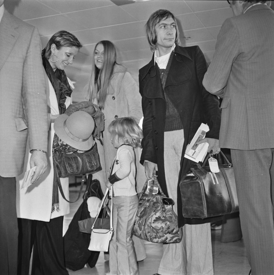 English drummer Charlie Watts of rock group the Rolling Stones at Heathrow Airport in London with his wife Shirley (left) and their daughter Seraphina, UK, 5th December 1972.  (Photo by Evening Standard/Hulton Archive/Getty Images)