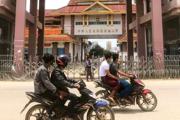 Motorists pass the China-Myanmar border gate in Muse in Shan state, as the Chinese city of Ruili near the frontier with Myanmar imposed a lockdown (AFP/STR)