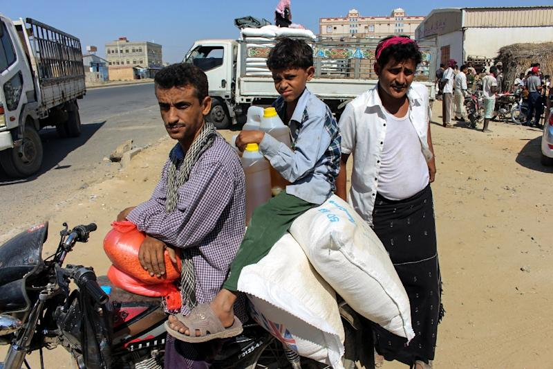 A man and child ride on a motorcycle loaded with sacks of wheat and cooking oil containers distributed as food aid by a local charity at a camp for the displaced, in the northern Yemeni province of Hajjah on December 23, 2017 (AFP Photo/STRINGER)