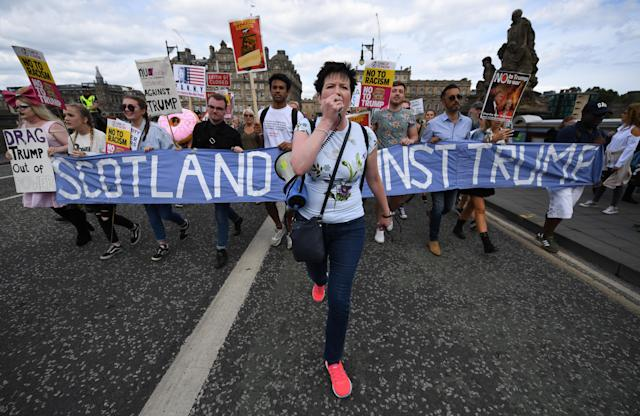 <p>A woman talks on a loudspeaker as people hold a large anti-Trump banner and other signs on July 14, 2018, in Edinburgh, Scotland. (Photo: Jeff J. Mitchell/Getty Images) </p>