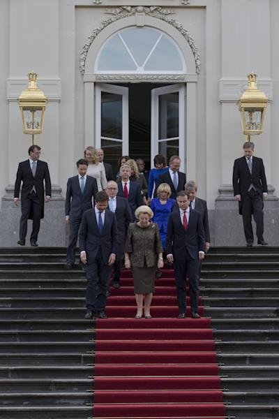 Dutch Queen Beatrix, center, Prime Minister Mark Rutte, center left, Deputy Prime Minister and Minister of Social Affairs and Employment Lodewijk Asscher, center right, walk down the stairts with other ministers of the new Dutch government prior to posing on the steps of Royal palace Huis Ten Bosch after their inauguration ceremony in The Hague, Netherlands, Monday Nov. 5, 2012. (AP Photo/Peter Dejong)