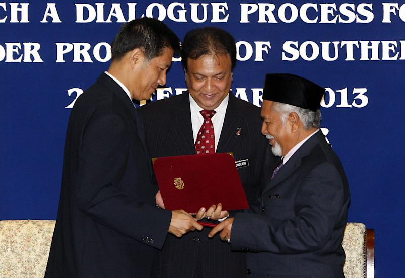 CORRECTS TO CLARIFY THAT THE NATIONAL REVOLUTION FRONT IS MALAYSIAN-BASED - Thailand's National Security Council Secretary General Paradorn Pattanathabutr, left, and Malaysian-based National Revolution Front chief Hassan Taib, right, exchange signed documents as Malaysia's National Security Council Secretary Mohamed Thajudeen Abdul Wahab witnesses during the signing ceremony of the general consensus document to launch a dialogue process for peace in the border provinces of southern Thailand, in Kuala Lumpur, Malaysia, Thursday, Feb. 28, 2013. Thai authorities and Muslim militant leaders based in neighboring Malaysia agreed Thursday to hold talks to help ease nearly a decade of unrest in southern Thailand. (AP Photo/Lai Seng Sin)