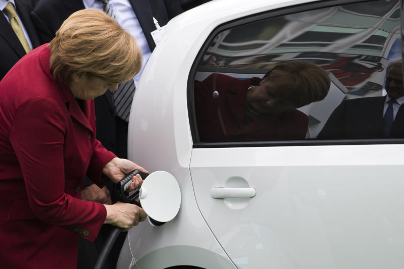 German Chancellor Angela Merkel plugs a charging nozzle into an electric car at the Electric Mobility Conference of the German government in Berlin May 27, 2013. Merkel has reaffirmed her target to bring one million electric cars onto German roads by the end of the decade, despite weak interest from consumers. REUTERS/Thomas Peter (GERMANY - Tags: TRANSPORT BUSINESS POLITICS)
