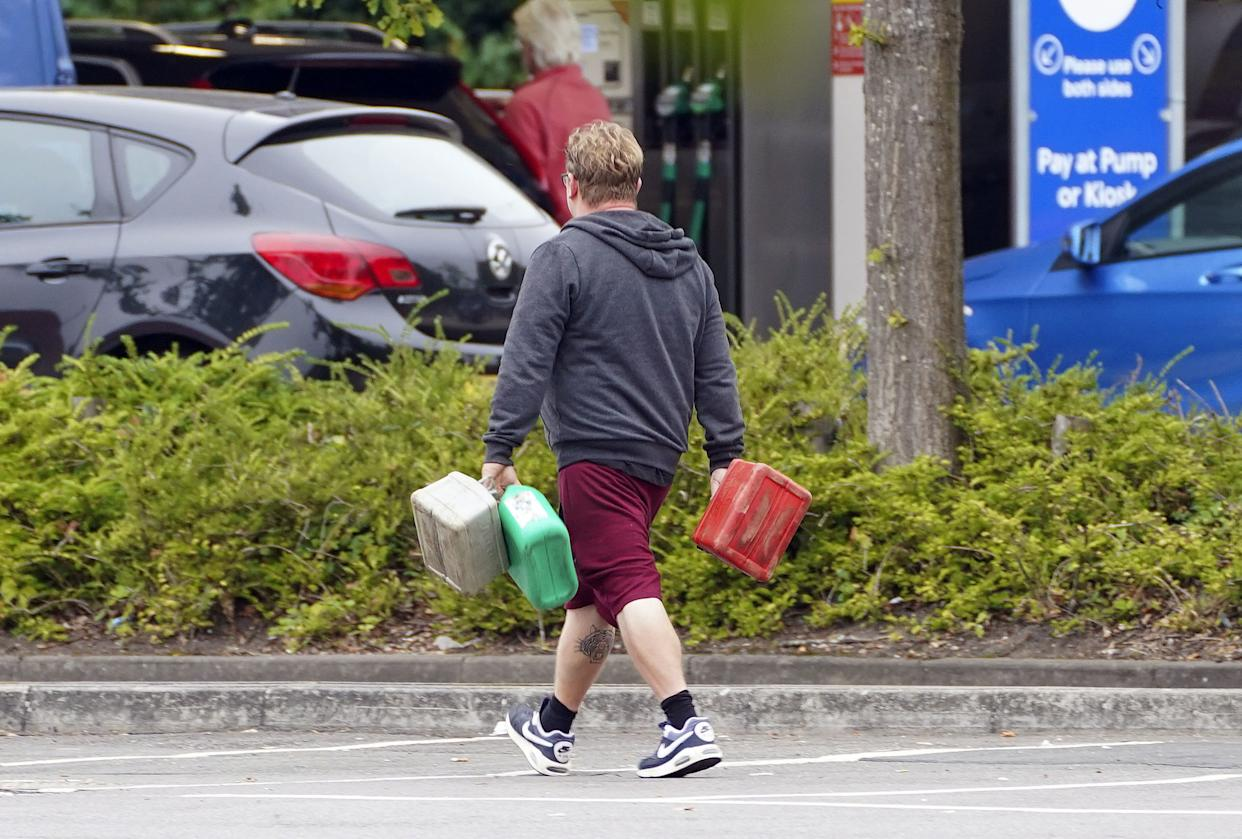A man carrying containers at a Tesco Petrol Station in Bracknell, Berkshire. Picture date: Saturday September 25, 2021.
