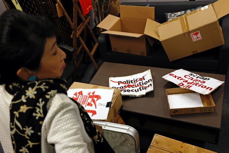 Legislator Claudia Mo sits in front of the protest placards and boxes at her office in Hong Kong