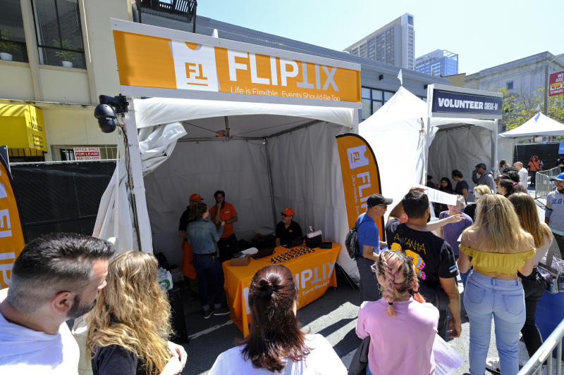 In this photo taken Friday, June 21, 2019, FlipTix CEO Jaime Siegel, seated, works at his company's tent at the entrance to the Clusterfest comedy event in San Francisco. The company's application lets people who leave a venue early sell their ticket and lets someone who wants the remainder of the ticket buy it.  Event organizers hoping to eliminate ticket scams and huge markups in the secondary market are increasingly turning to companies that use technology to allow fans to buy and resell their tickets while putting caps on prices.(AP Photo/Eric Risberg)