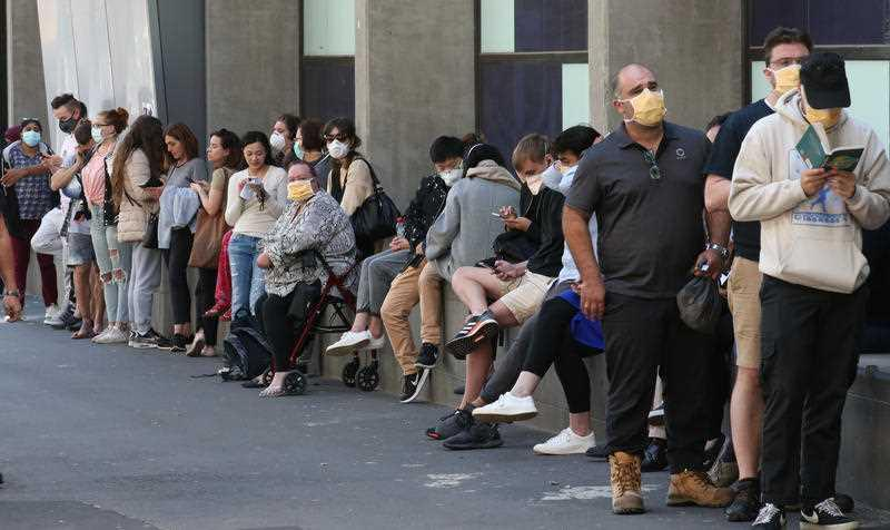 People line up outside the Royal Melbourne Hospital for coronavirus testing in Melbourne.