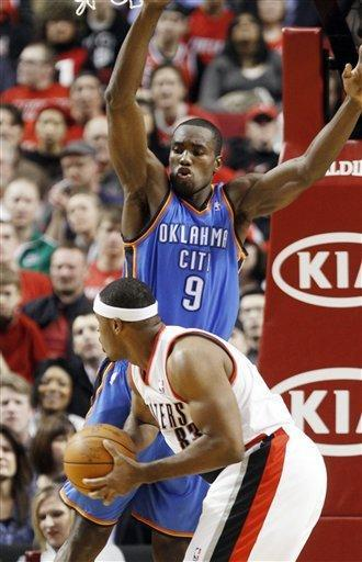 Oklahoma City Thunder forward Serge Ibaka, right, from Congo, defends against Portland Trail Blazers forward Craig Smith during the first half of their NBA basketball game in Portland, Ore., Monday, Feb. 6, 2012.(AP Photo/Don Ryan)