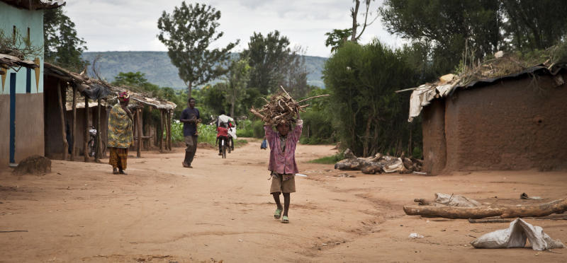 In this photo taken Tuesday, April 16, 2013, a Rwandan refugee child carries firewood in the Nakivale refugee camp in Uganda. Nearly two decades after the Rwandan genocide, thousands of refugees living in the camp in Uganda say they fear being forced to return to their home country. (AP Photo/Rebecca Vassie)