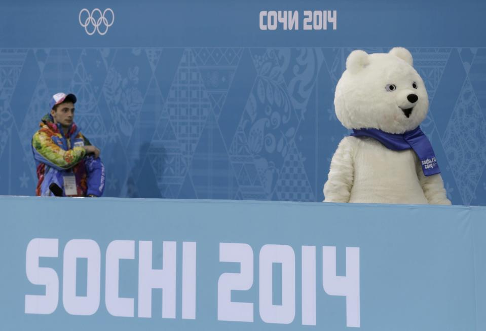 A volunteer looks at the polar bear mascot of the 2014 Sochi Olympics Games at the Ice Cube Curling Centre in Sochi February 11, 2014. REUTERS/Ints Kalnins (RUSSIA - Tags: SPORT OLYMPICS SPORT CURLING)
