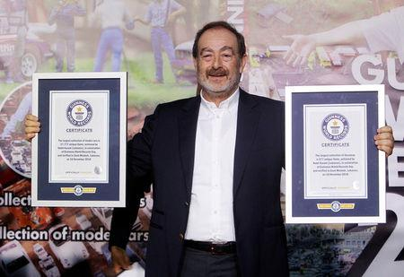 Nabil Karam poses with his Guinness World Record certificates for the largest collection of model cars and the largest collection of dioramas, in celebration of the Guinness World Records Day in Zouk Mosbeh, north of Beirut, Lebanon November 16, 2016. REUTERS/Aziz Taher