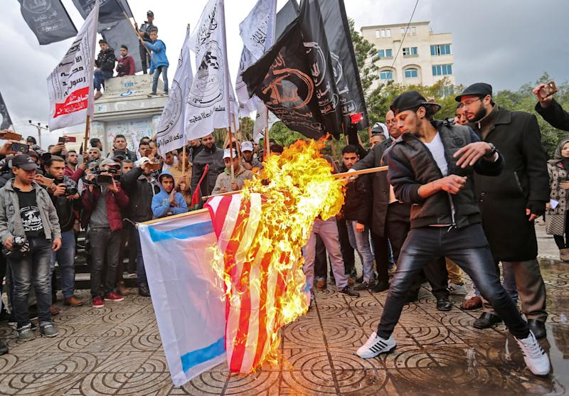 Palestinian protesters burn the U.S. and Israeli flags in Gaza City on December 6, 2017.
