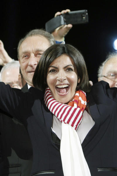 French Socialist Party deputy mayor of Paris, Anne Hidalgo smiles as outgoing mayor Bertrand Delanoe, stands behind her, during a speech after results were announced in the second round of the French municipal elections, in Paris, Sunday, March 30, 2014. Hidalgo saved Paris for the flagging Socialist Party in Sunday's municipal elections, becoming the French capital's first female mayor. (AP Photo/Thibault Camus)